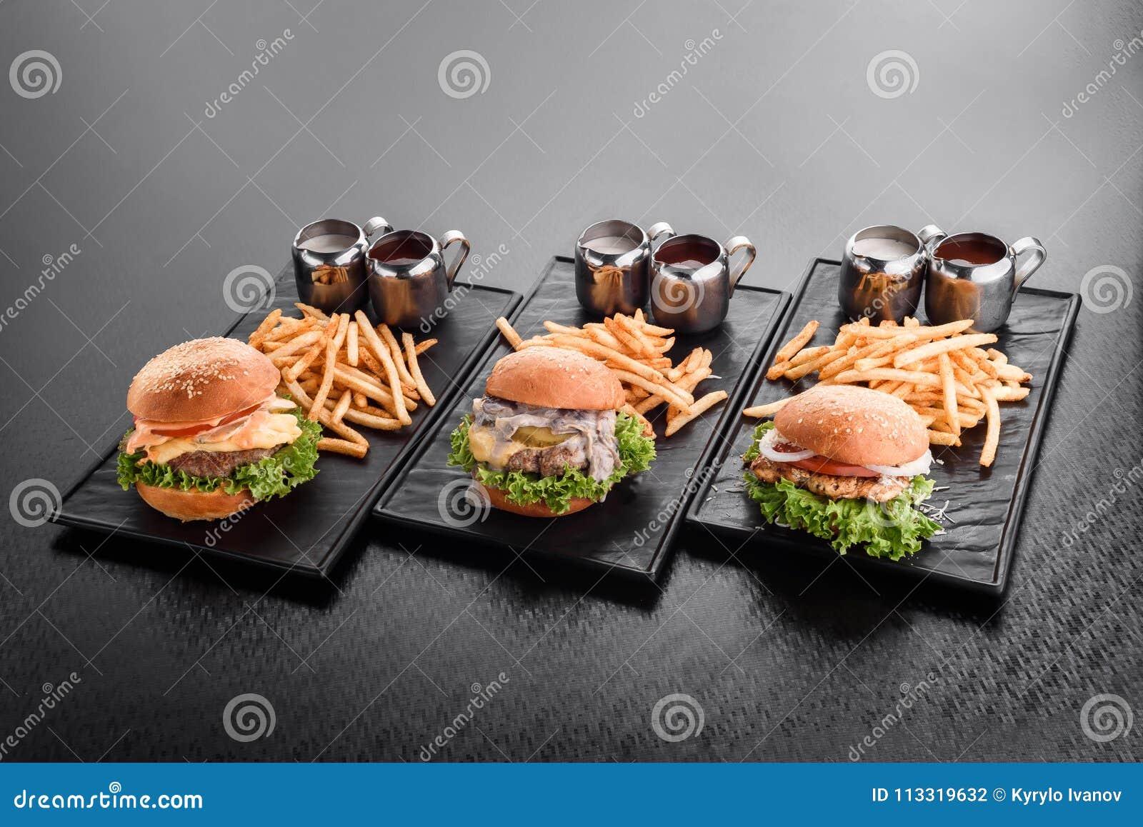 Różnorodni hamburgery z francuskimi dłoniaków hamburgerami na talerzu