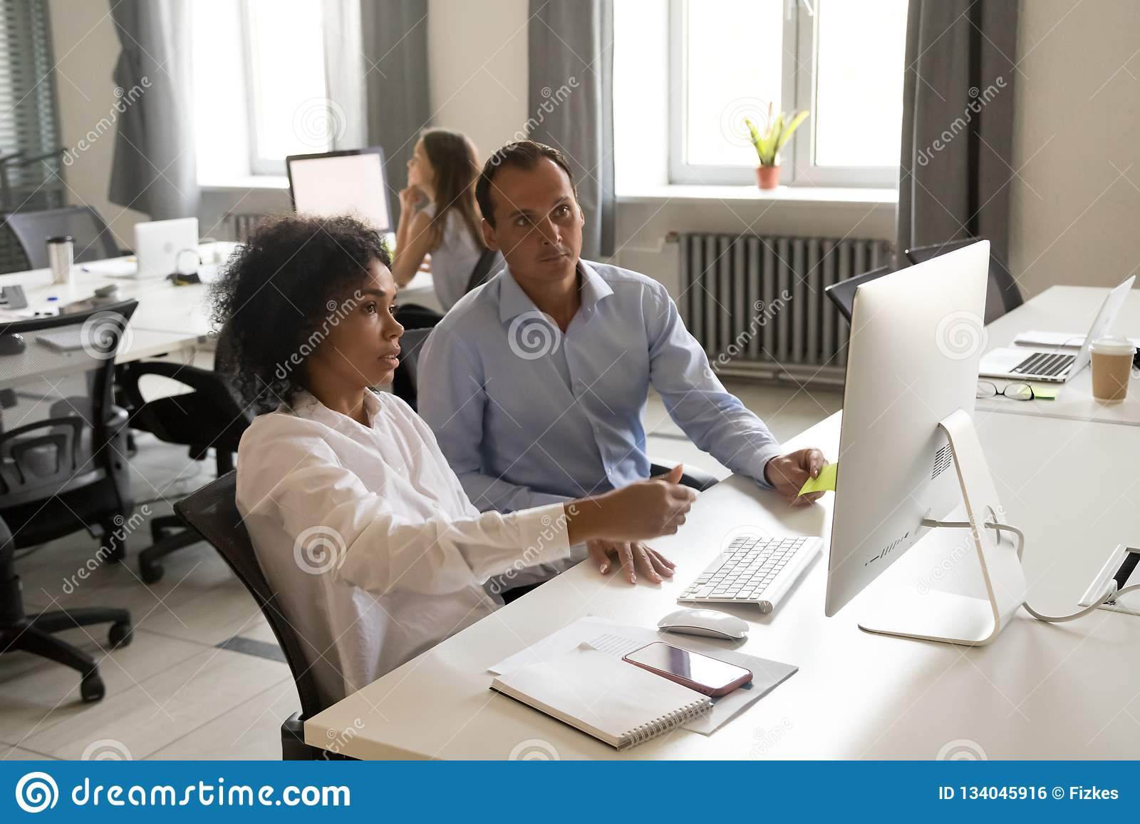 Różnorodni koledzy dyskutuje online ich pracę wpólnie
