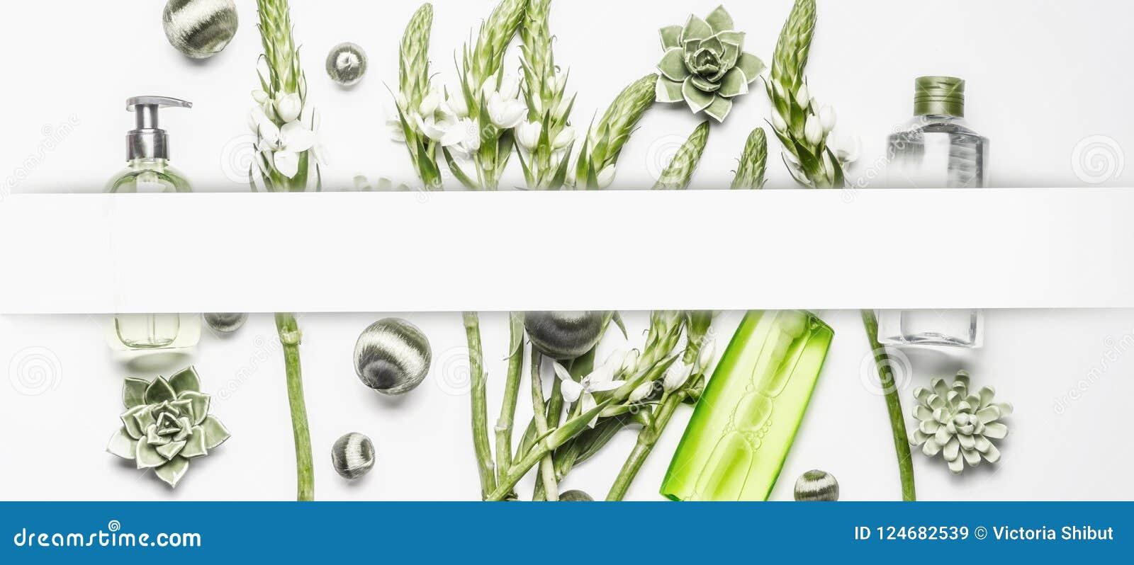 Różnorodni kosmetyczni produkty z zielonymi kwiatami i roślinami na białym tle, rama