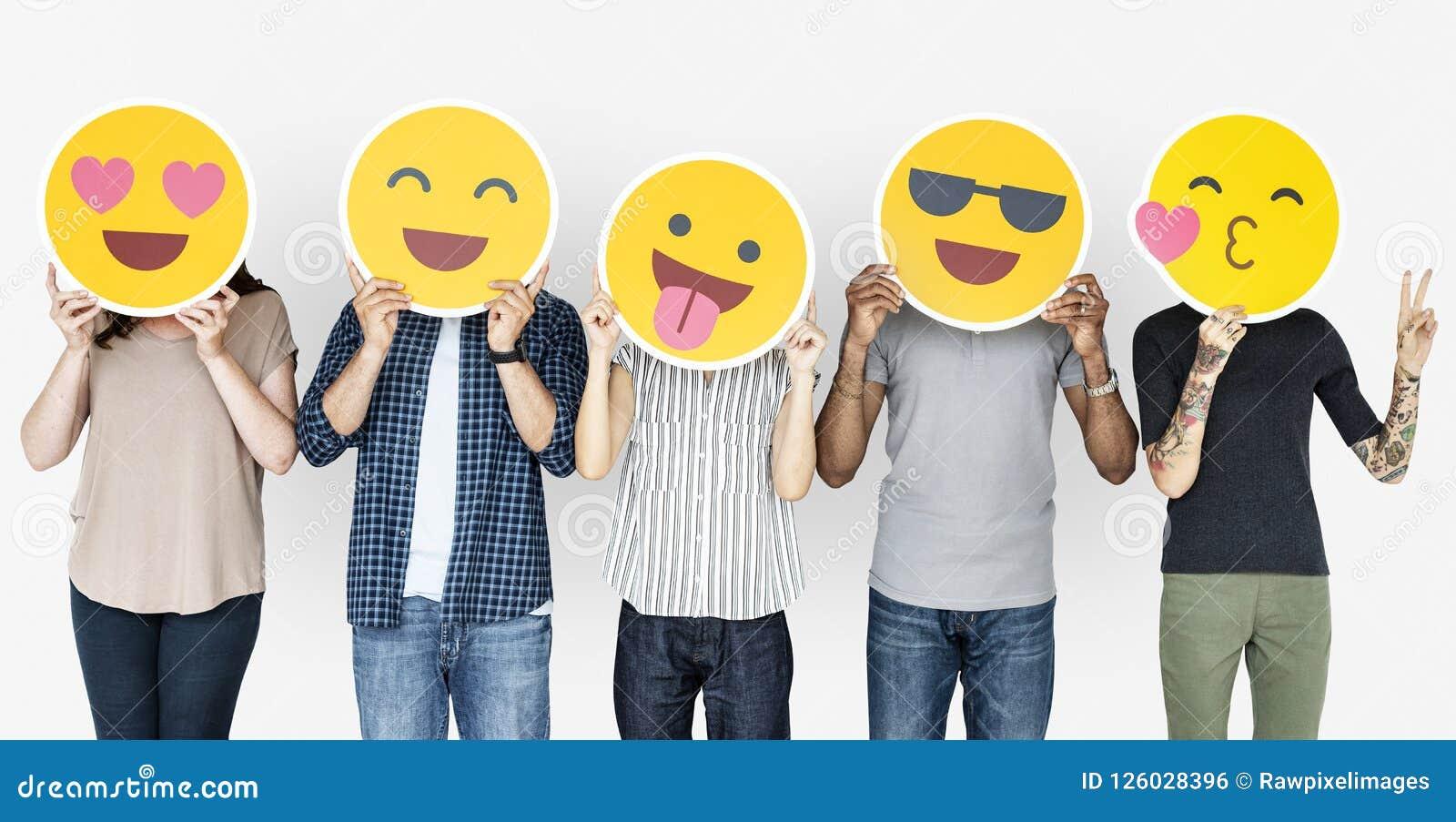 Różnorodni ludzie trzyma szczęśliwych emoticons