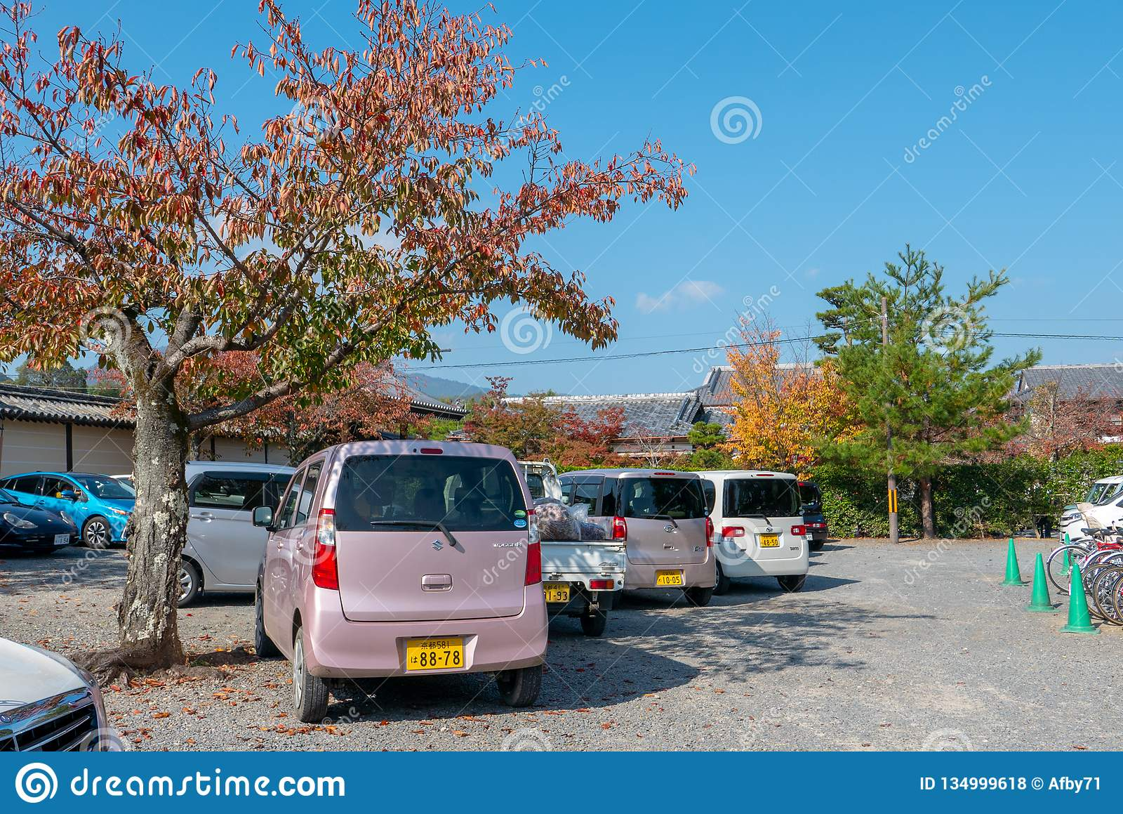 Różnorodny Kei samochodów park pod drzewami podczas jesieni w Arashiyama, Japonia