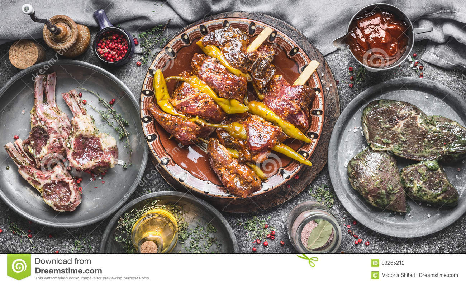 Różnorodny mięso dla grilla: mięśni skewers, baranek dręczą ziobro i marynowanych stki na nieociosanym kuchennego stołu tle, odgó