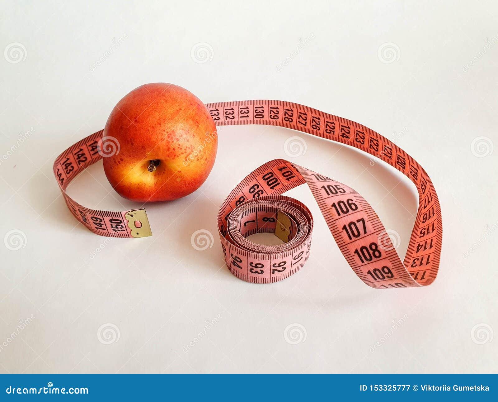 Różowa miara taśmy z czerni liczbami na białym naturalnym tle z smołą Zamyka w górę widoku pomiarowa taśma Temat: dieta,