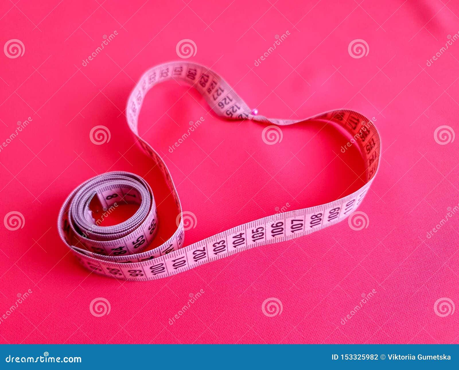 Różowa miara taśmy z czerni liczbami na tkaniny tle Zamyka w górę widoku pomiarowa taśma Tematy: dieta, handmade, domowy wystrój,