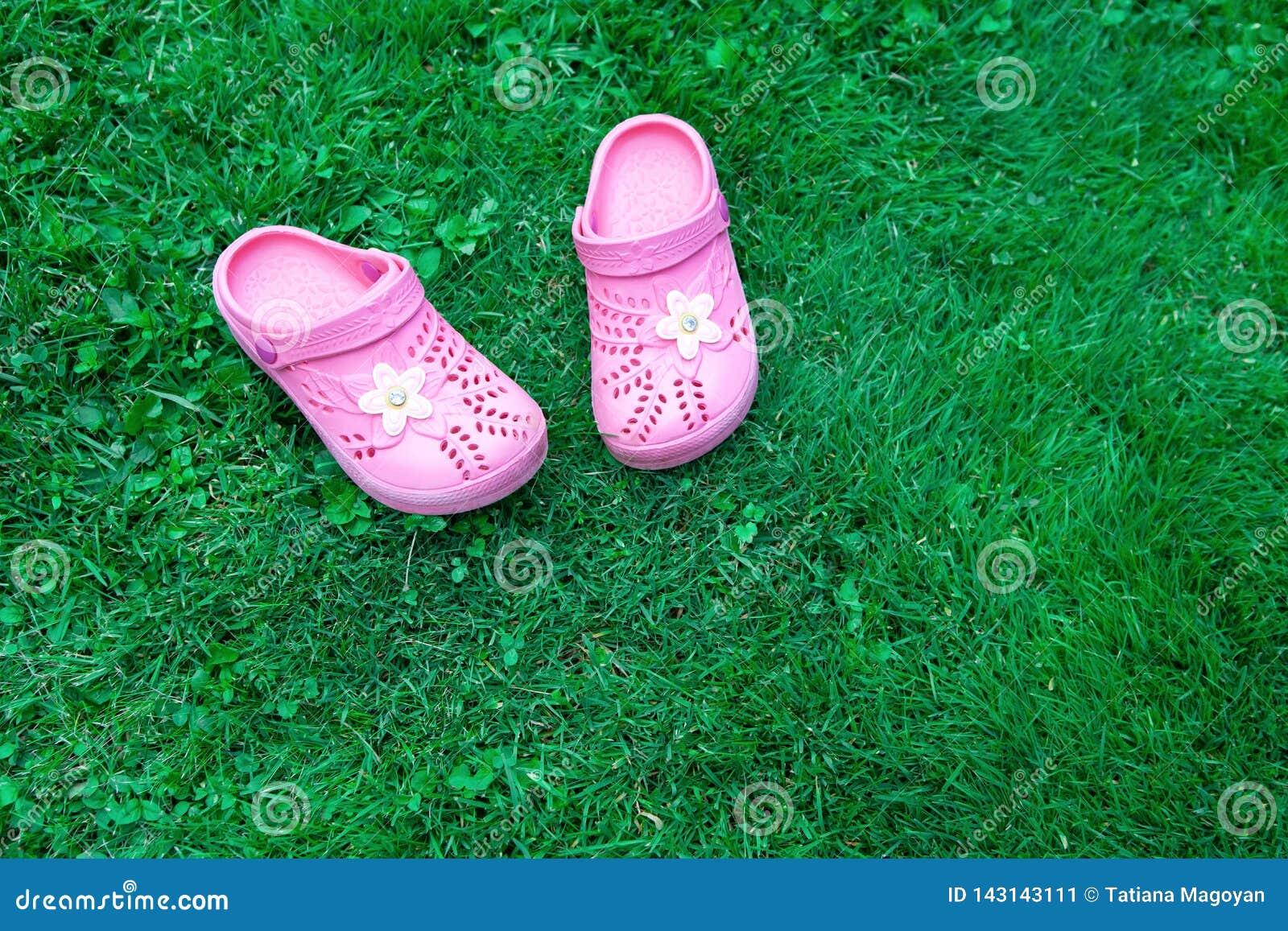 Różowi dzieciaków kapcie na zielonym gazonie kosmos kopii Odgórny widok, lokalizować przy stroną rama horyzontalny Pojęcie jednoś