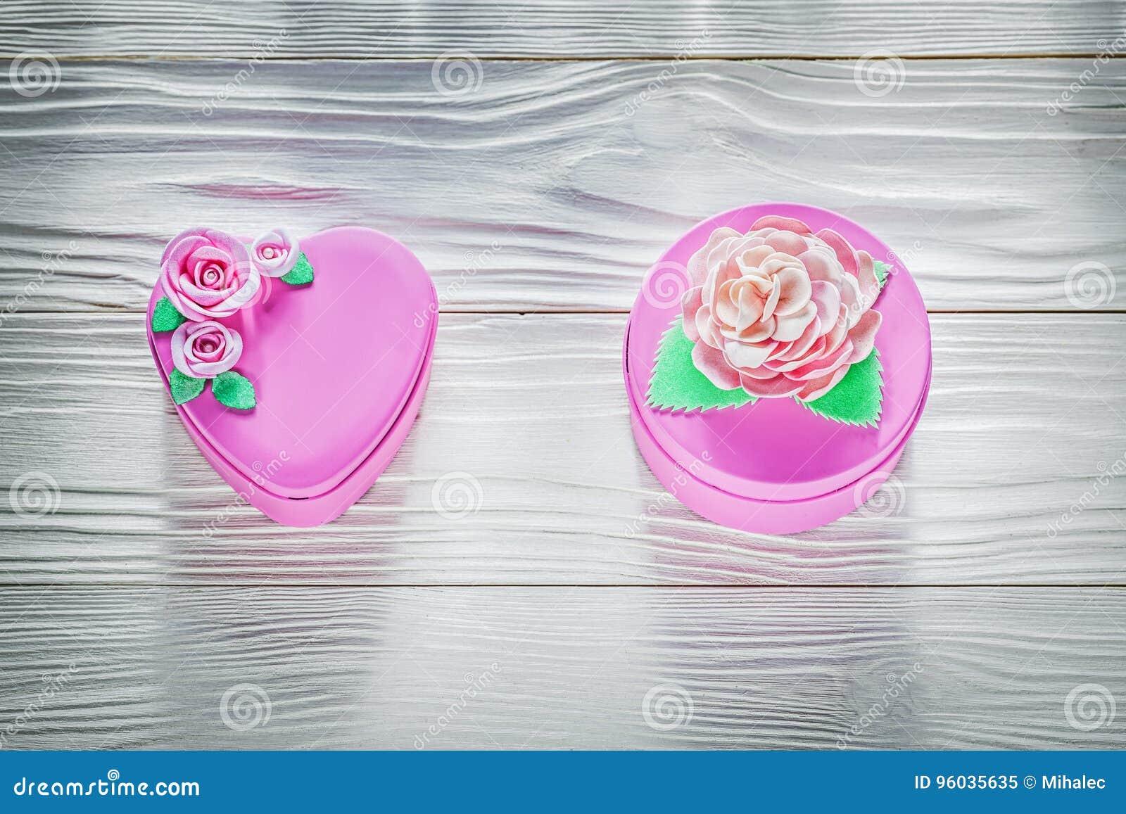 Różowi metalu prezenta pudełka na drewnianej deski świętowań pojęciu