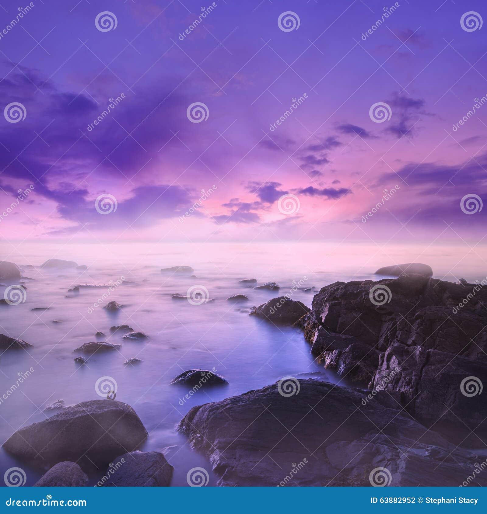 Różowy i Purpurowy zmierzch Nad Mglistymi skałami w morzu