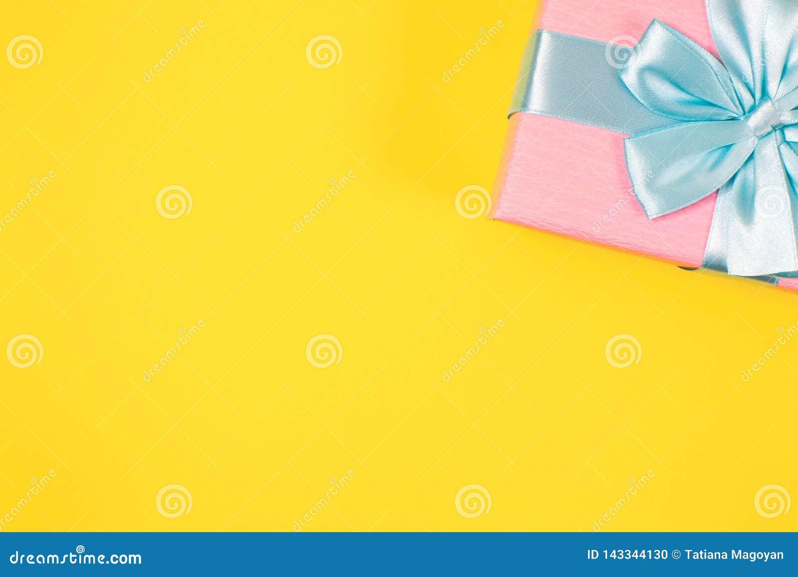 Różowy prezenta pudełko wiązał z błękitnym faborkiem z łękiem przy wierzchołkiem na żółtym tle Odbitkowa przestrzeń dla teksta Mi