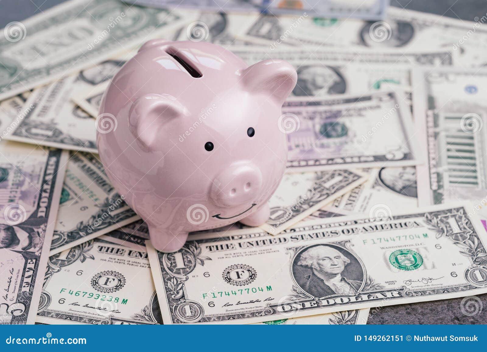 Różowy prosiątko bank lub menniczy bank na stosie dolarów amerykańskich banknotów pieniądze, inwestorski przyrost, pieniężny tło