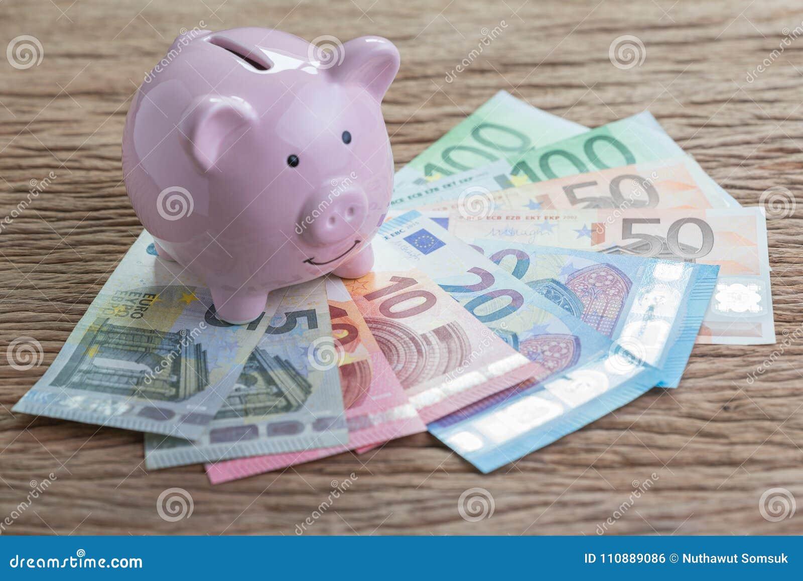 Różowy prosiątko bank na stosie Euro banknoty na drewnianym stole, finan