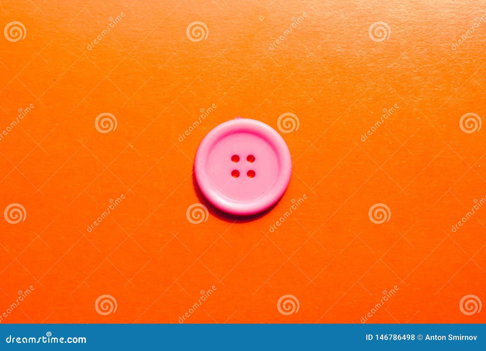Różowy retro guzik na pomarańczowym tle Minimalny pojęcie z guzikiem