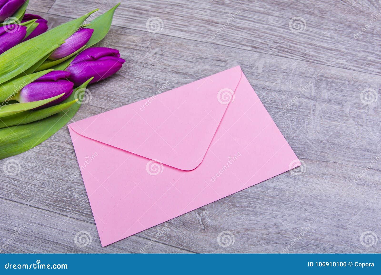 Różowa koperta z tulipanami na stole