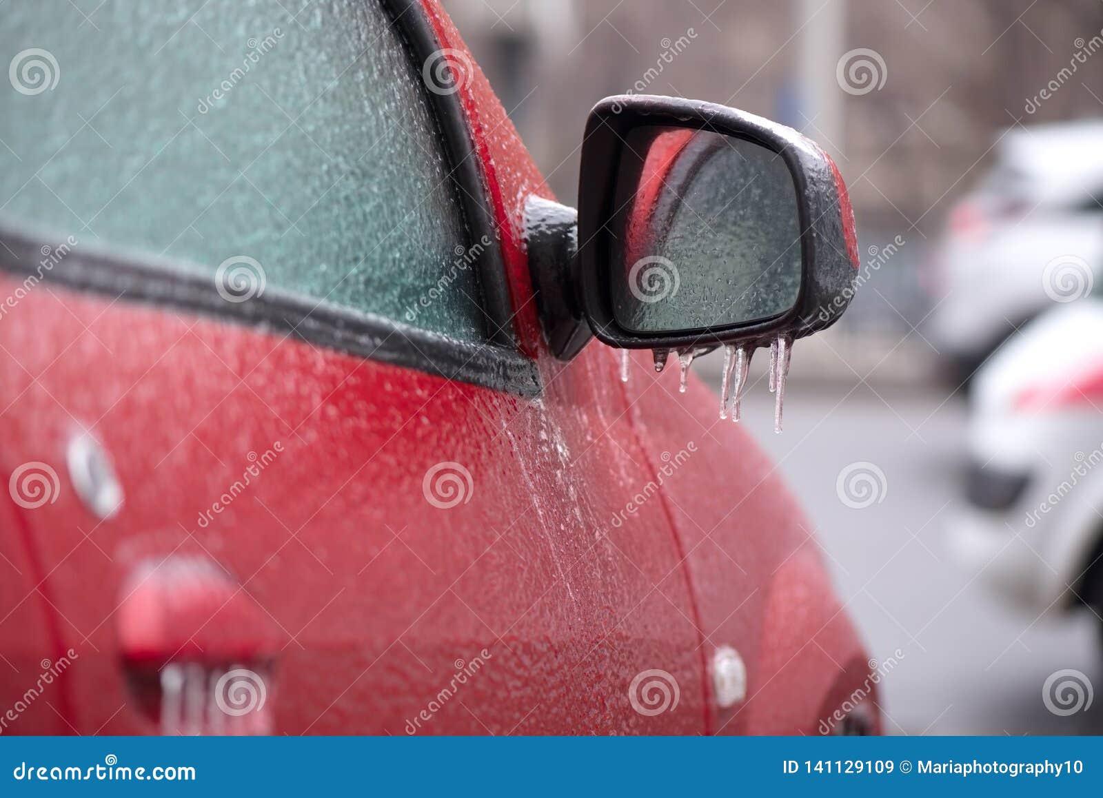 Röd bil som täckas med is
