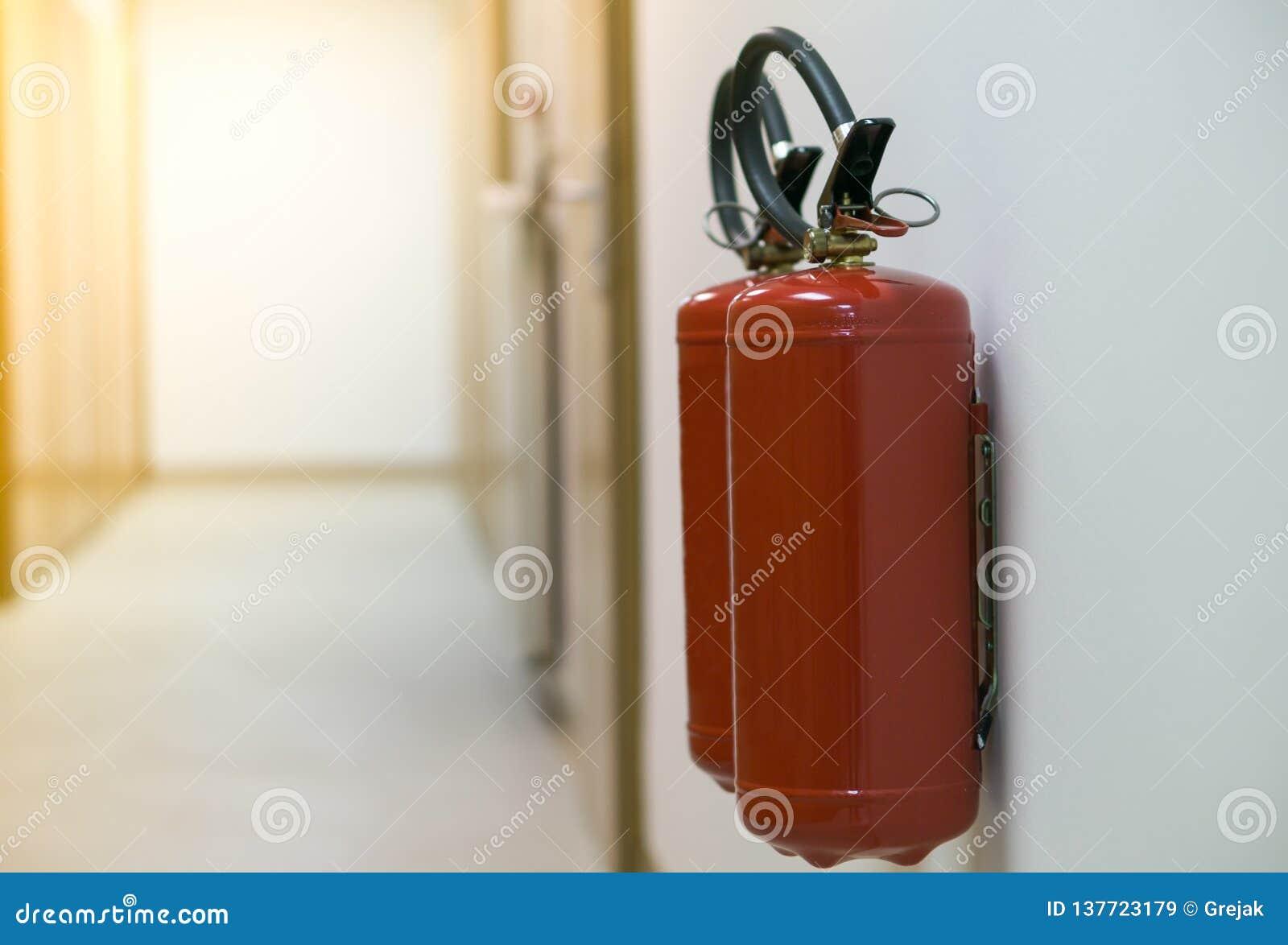 Röd brandsläckare i tom korridor på den vita väggen med solsignalljuset