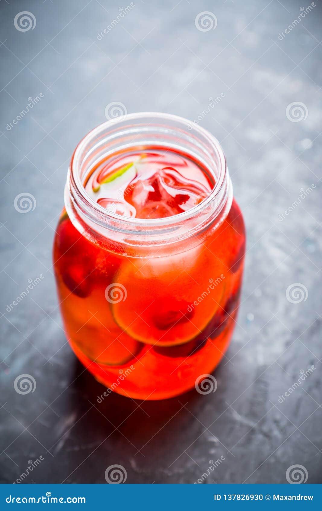 Röd coctail med körsbäret och limefrukt i krus på den lantliga bakgrunden