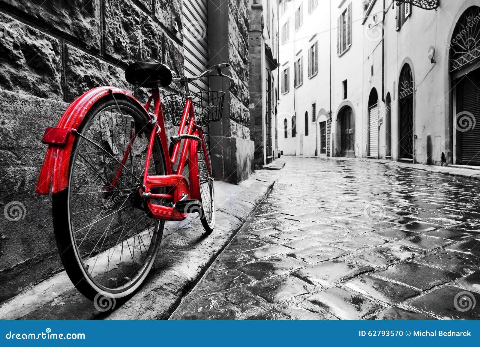 Röd cykel för Retro tappning på kullerstengatan i den gamla staden Färg i svartvitt