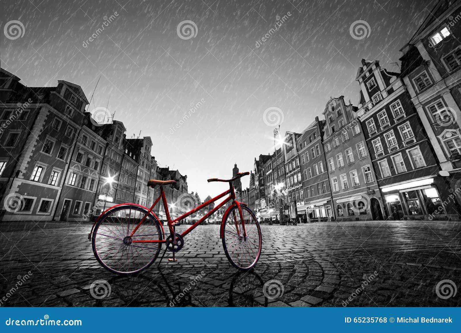 Röd cykel för tappning på historisk gammal stad för kullersten i regn poland wroclaw