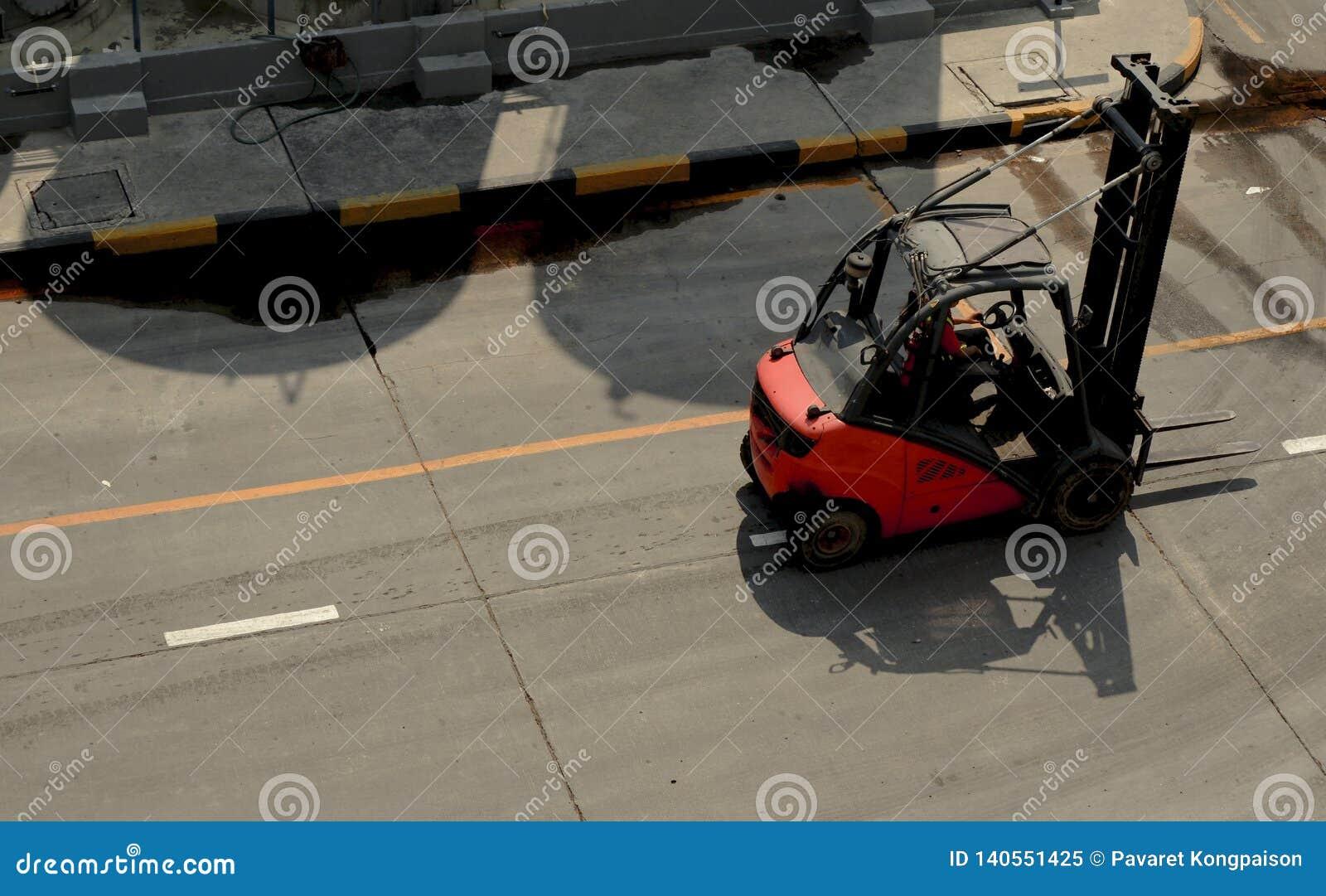 Röd gaffeltruck på fabriksvägen