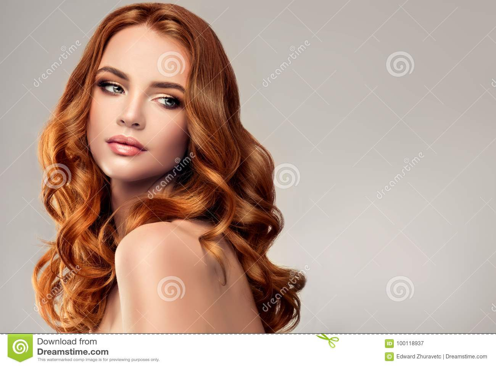 Röd haired kvinna med den omfångsrika, skinande och lockiga frisyren attraktiv bakgrundshårkam som flyger grått hårladybarn
