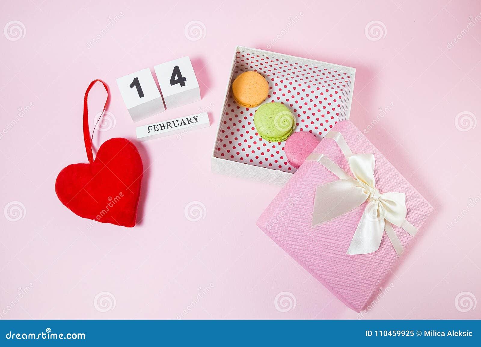 Röd hjärta med träkalendern och macarons i den rosa gåvaasken