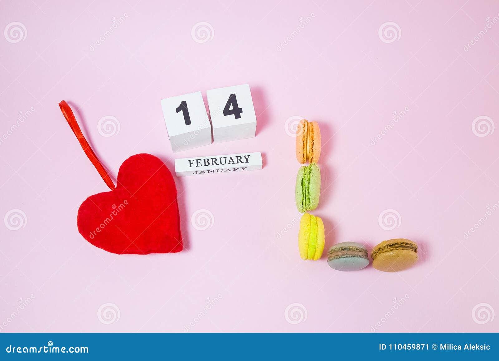 Röd hjärta med träkalendern och macarons i form av bokstäver L simbol av förälskelse