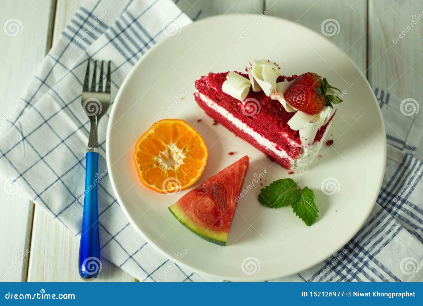 Röd jordgubbekaka som förläggas på plattan