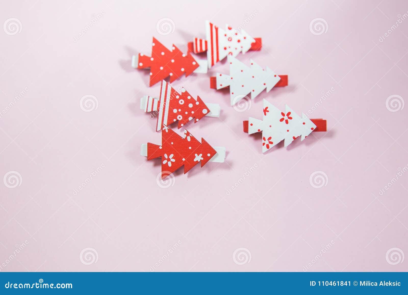 Röd jul och vitklämmor på rosa bakgrund ekologiskt trä för julgarneringar close upp