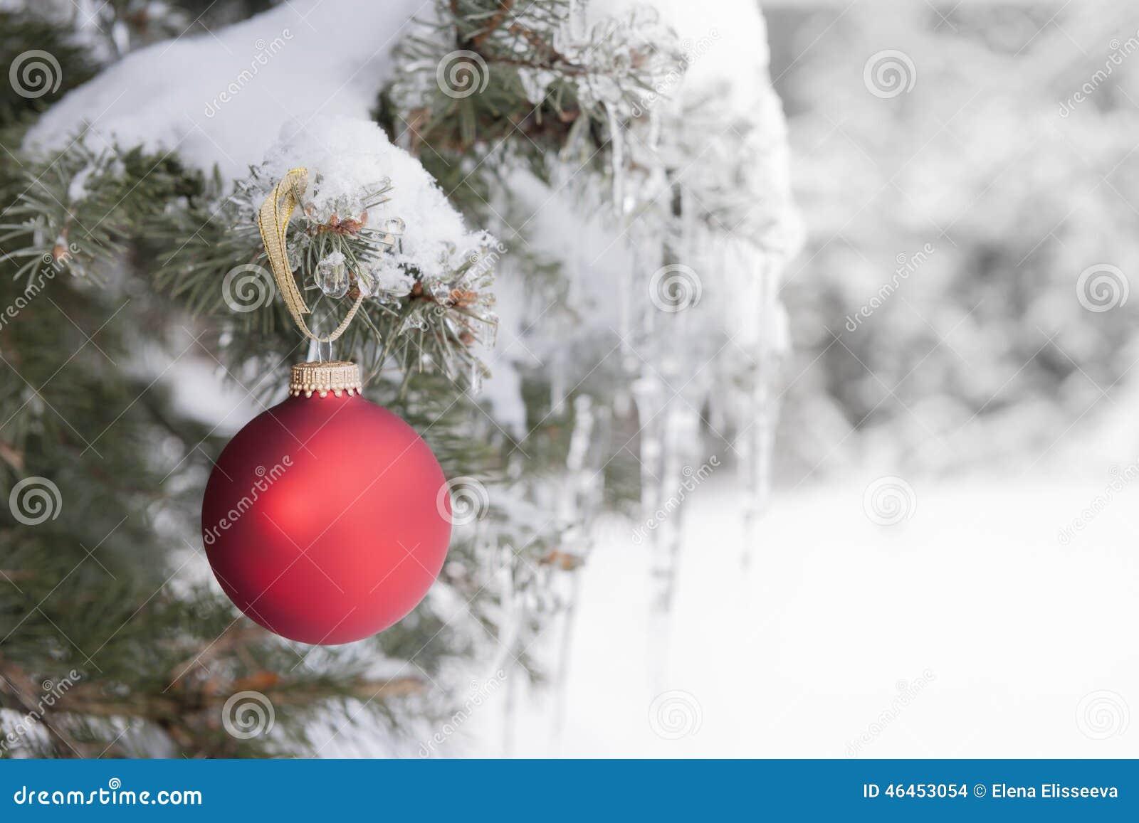 Röd julprydnad på snöig träd