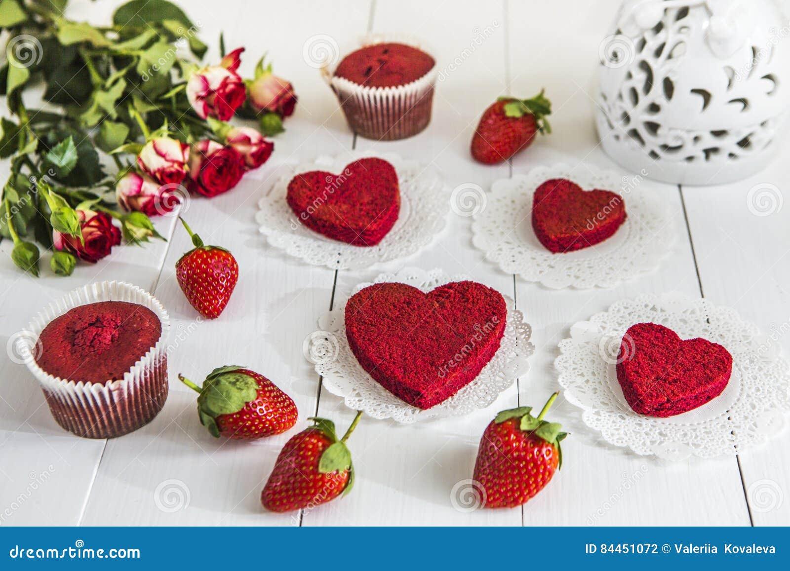 Röd kaka utan röd sammet` för kräm- ` på en vit trätabell som dekoreras med för den rosor och vit openwork vasen för jordgubbar,