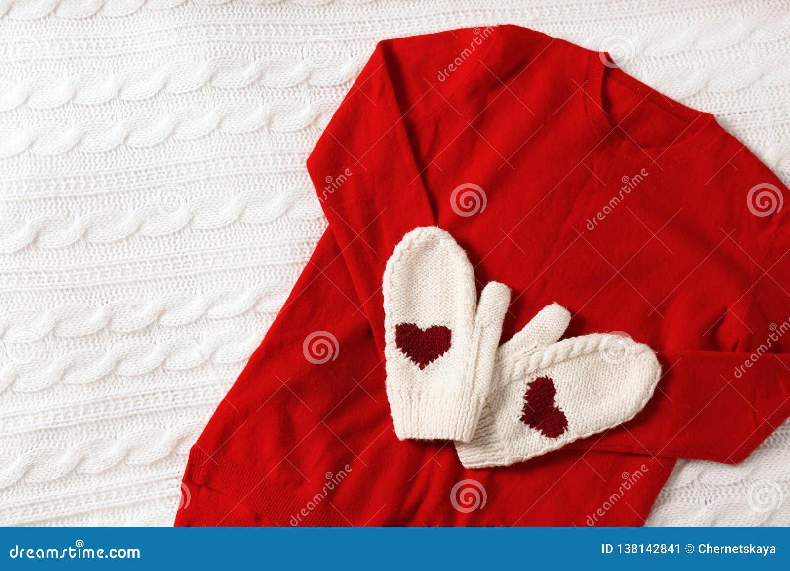 Röd kaschmirtröja och tumvanten på den stack plädet