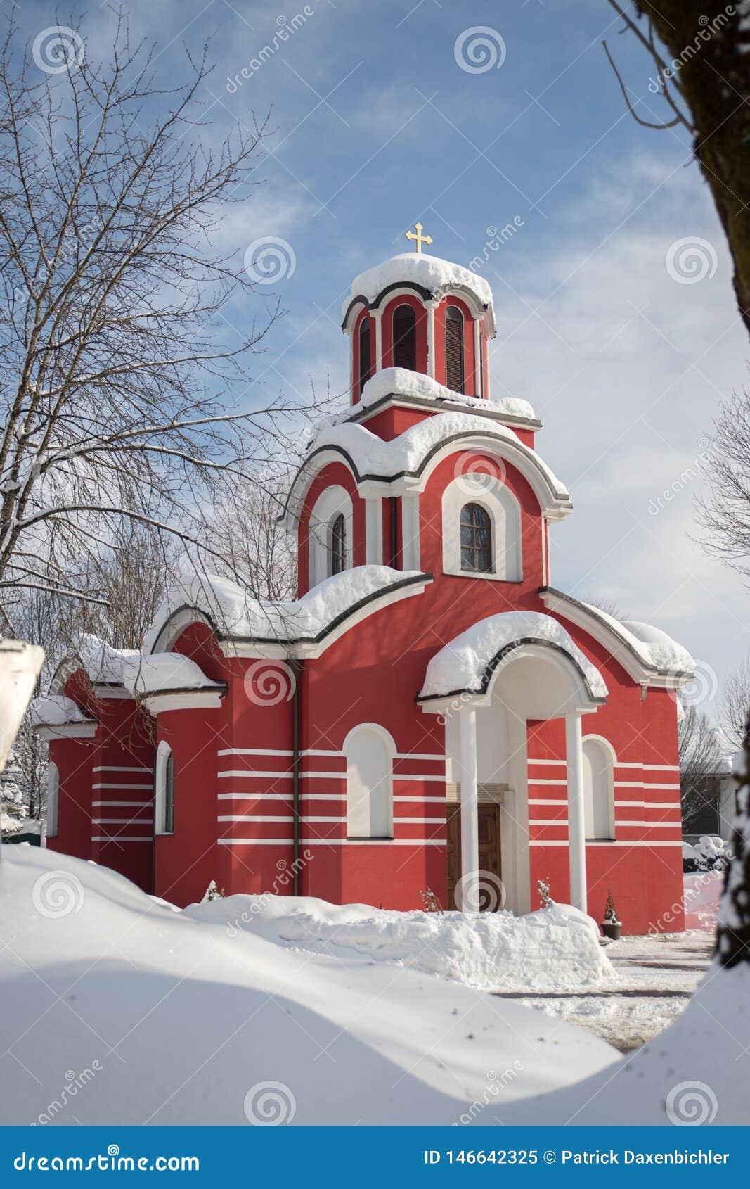Röd kristen kyrka i vintern, snö på taket