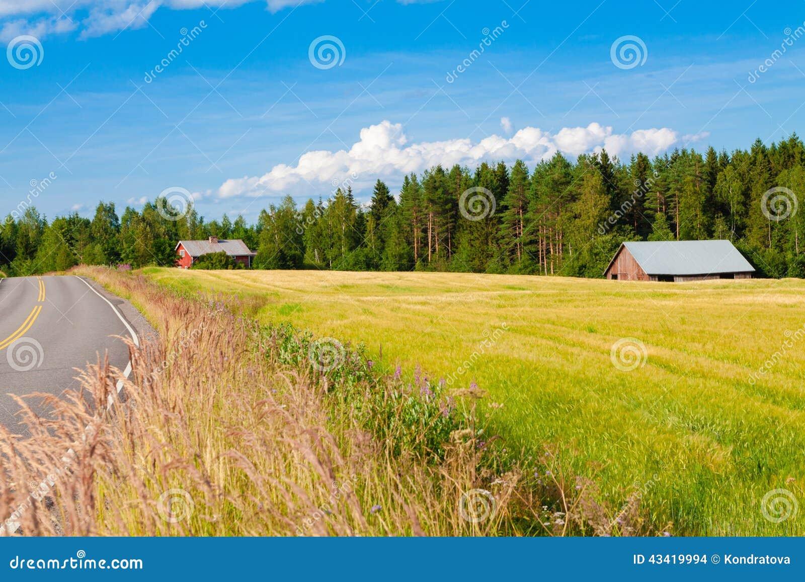 Röd lantgård med vägen, den blåa himlen och det gröna fältet