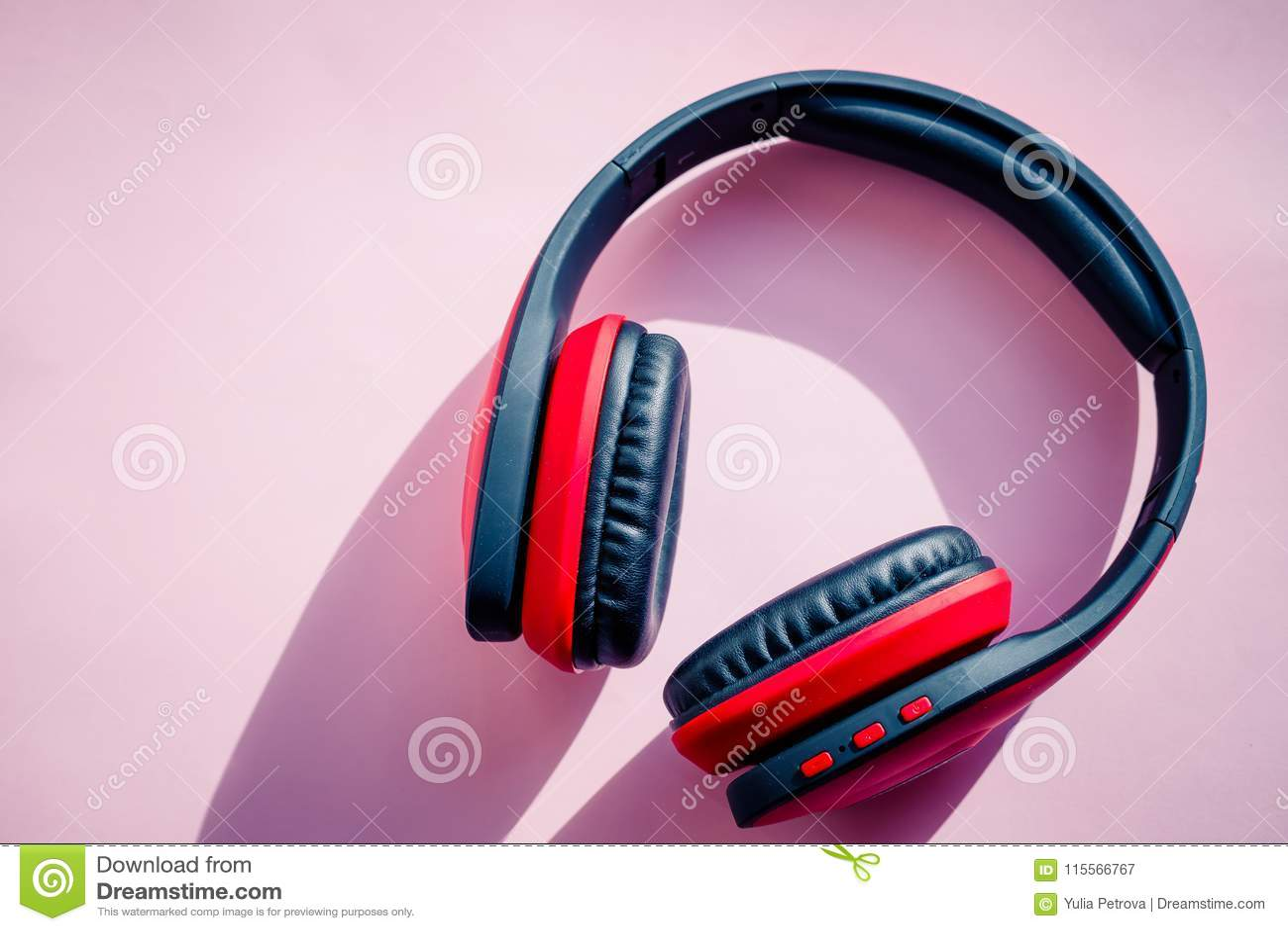 Röd och svart hörlurar på rosa bakgrund lyssnar musik Minimalismidébegrepp