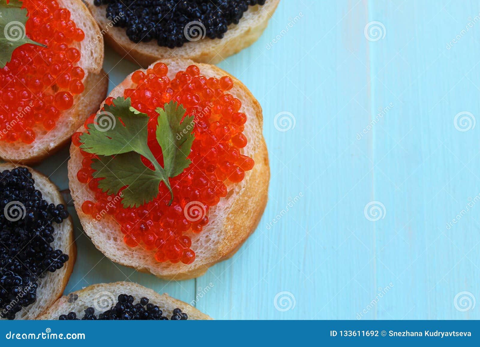 Röd och svart kaviar av fisklögner på vetebröd