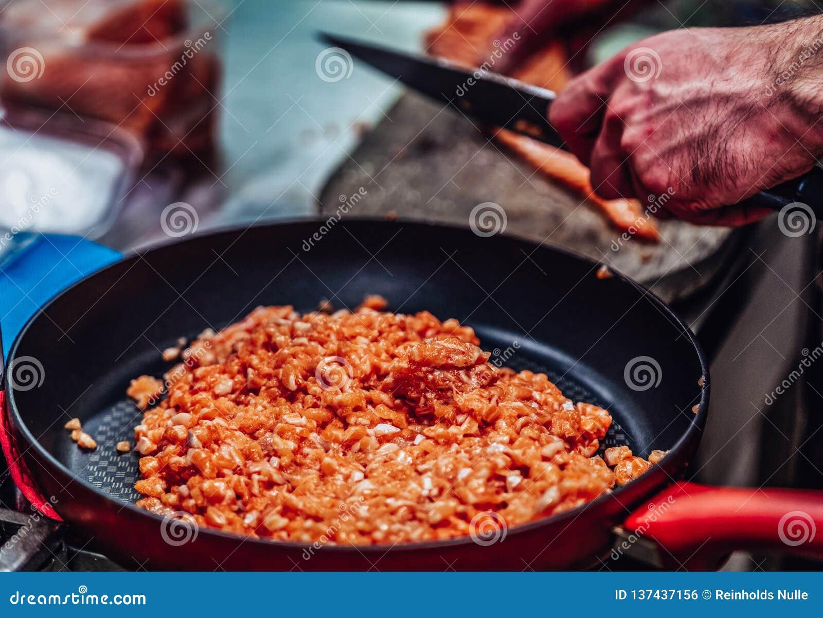 Röd panna med högen av snittet Salmon Pieces i förgrunden, manlig kock Cutting Fresh Salmon på träbrädet i bakgrunden -