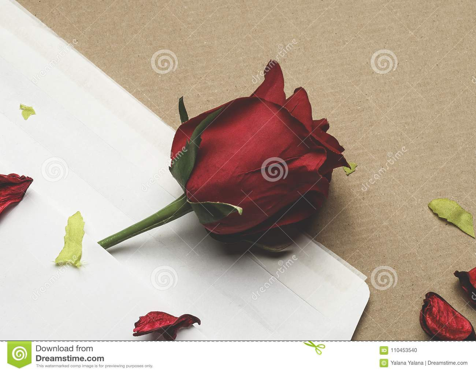 Röd ros i ett kuvert på ett ljus - brun bakgrund