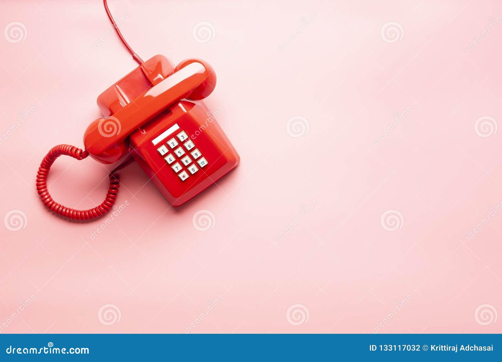 Röd telefon på det rosa skrivbordet