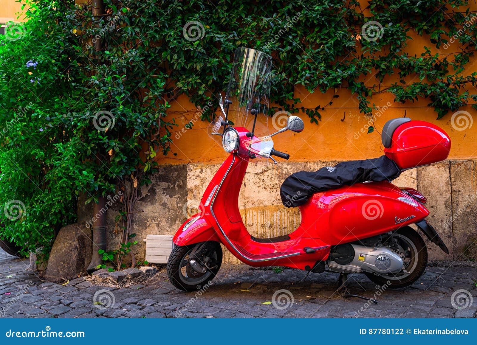 Röd Vespasparkcykel som parkeras på den gamla gatan i Rome, Italien