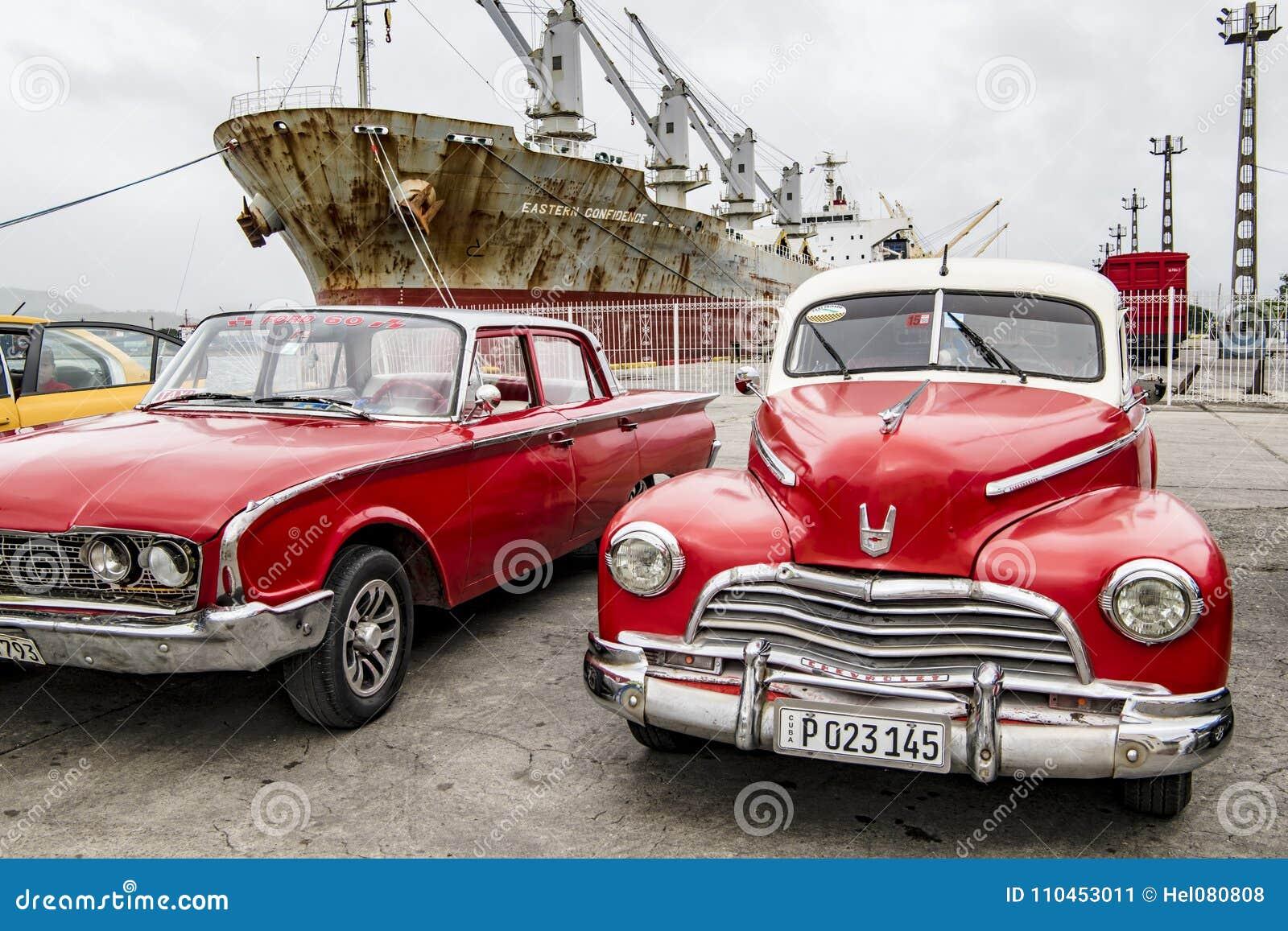 Röda amerikanska klassiska bilar och rostigt skepp, Santiago de Cuba
