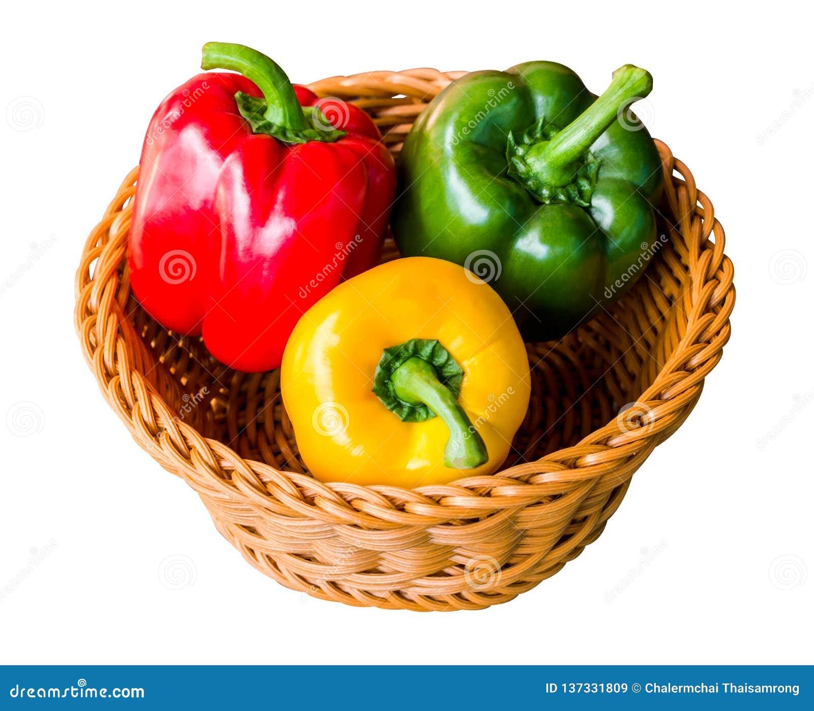 Röda, gröna och gula söta spanska peppar i en korg som isoleras på vit bakgrund med urklippbanan