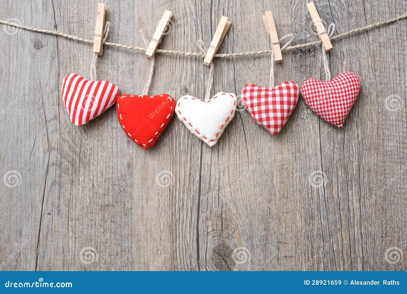 Röda hjärtor som hänger över wood bakgrund