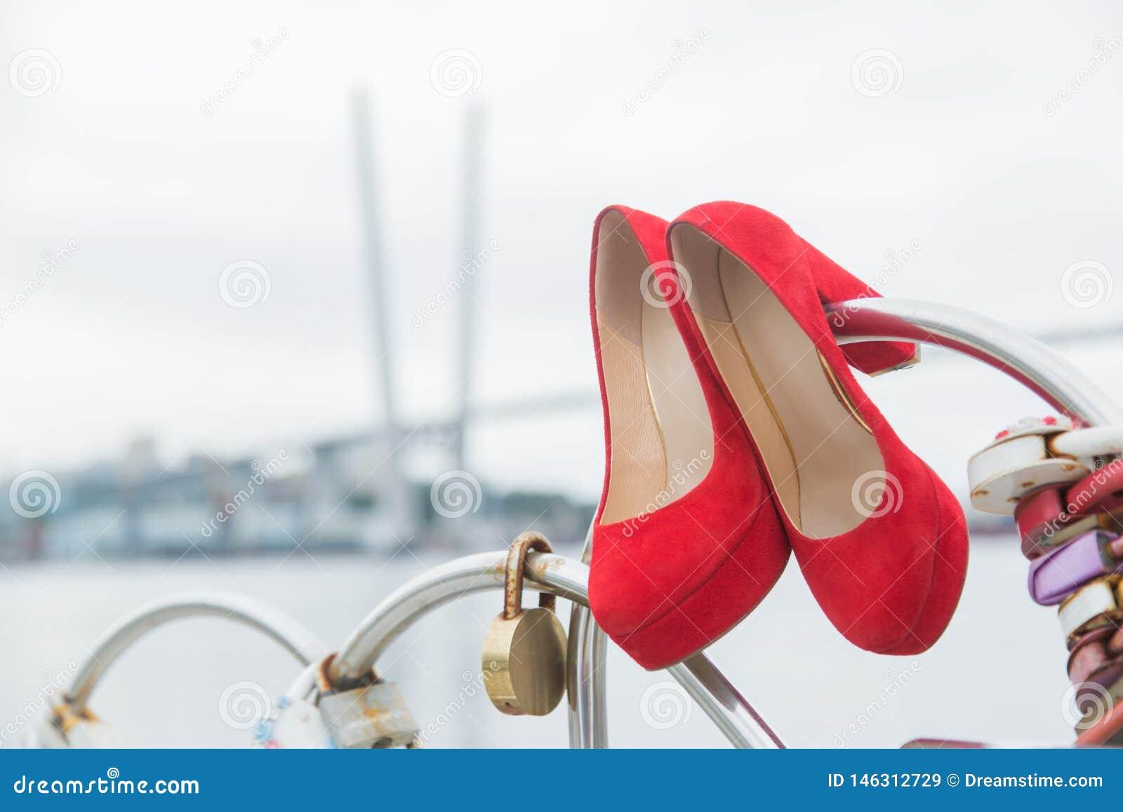 Röda lyxiga skor som hänger på staketet med lås av hjärtor mot himlen