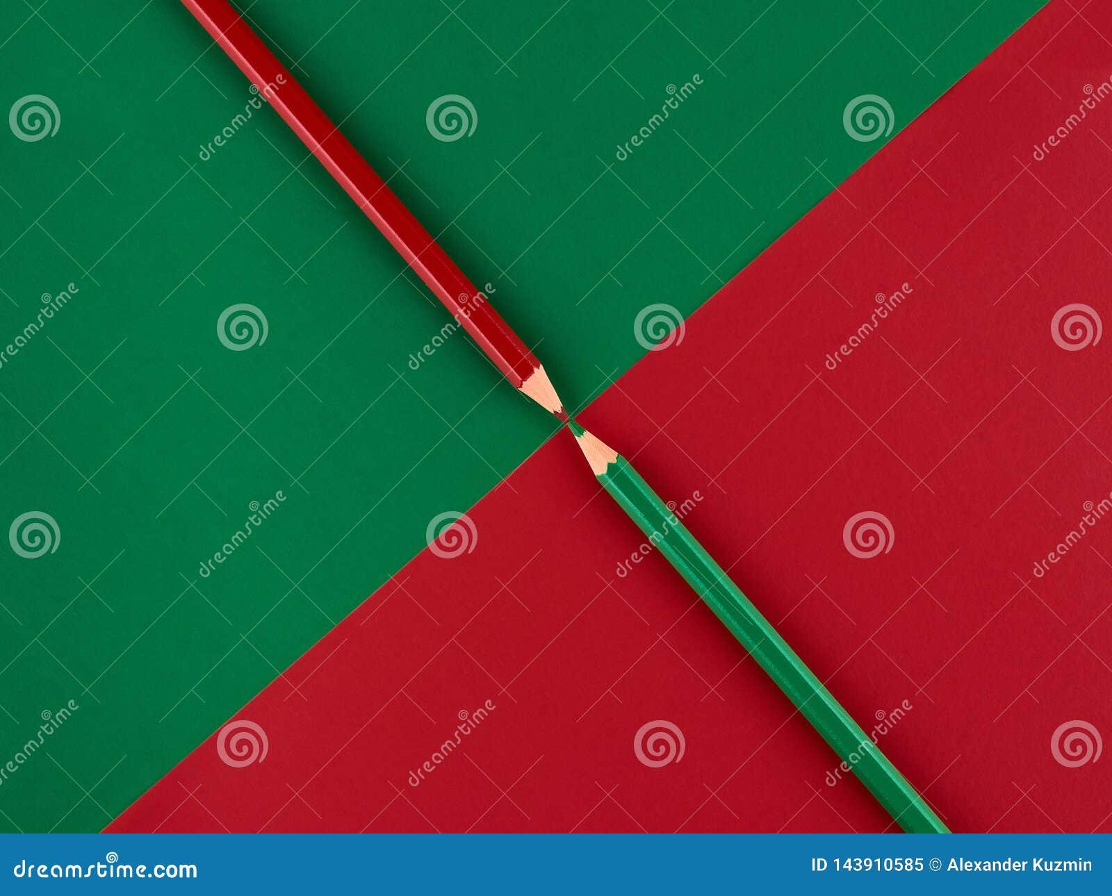 Röda och gröna blyertspennor på en kontrastera bakgrund