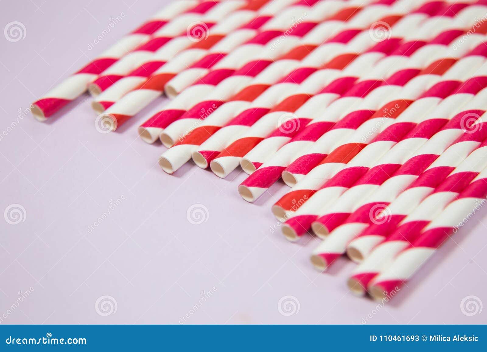 Röda och orange sugrör på den rosa bakgrunden