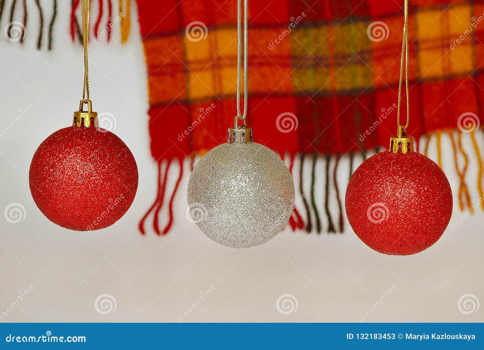 Röda och silverjulbollar mot en woolen röd och gul rutig halsduk med en frans Begrepp av ferier, jul och N