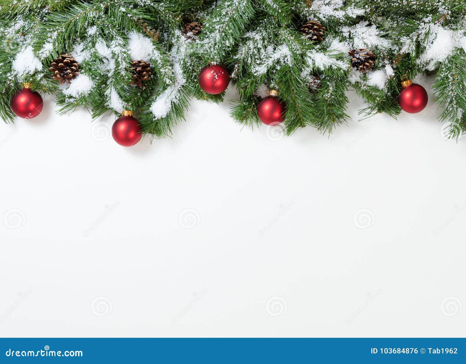 Röda prydnader för snöig jul som hänger i granträdfilialer