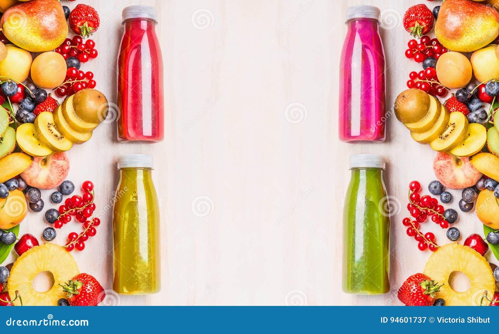 Röda, rosa, gröna och gula smoothies och fruktsaftdrycker i flaskor med olika nya organiska frukter och bäringredienser på w
