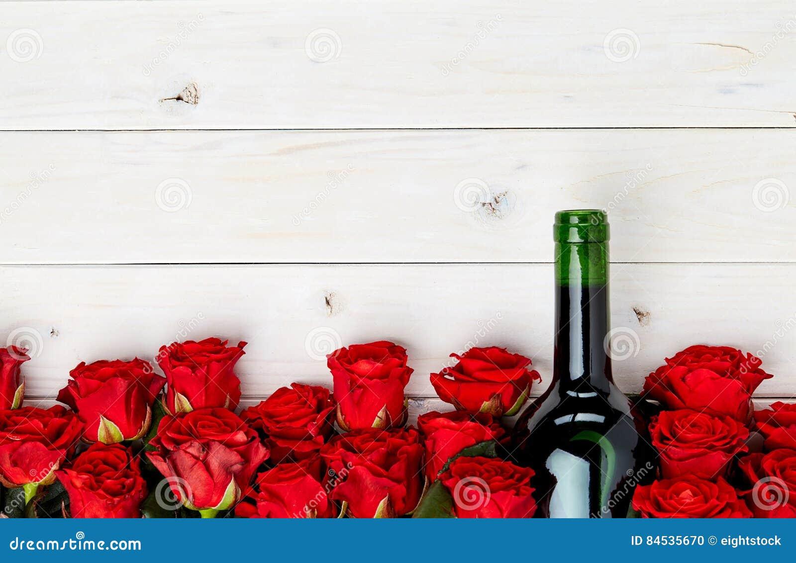 Röda rosor och vin på vit bakgrund