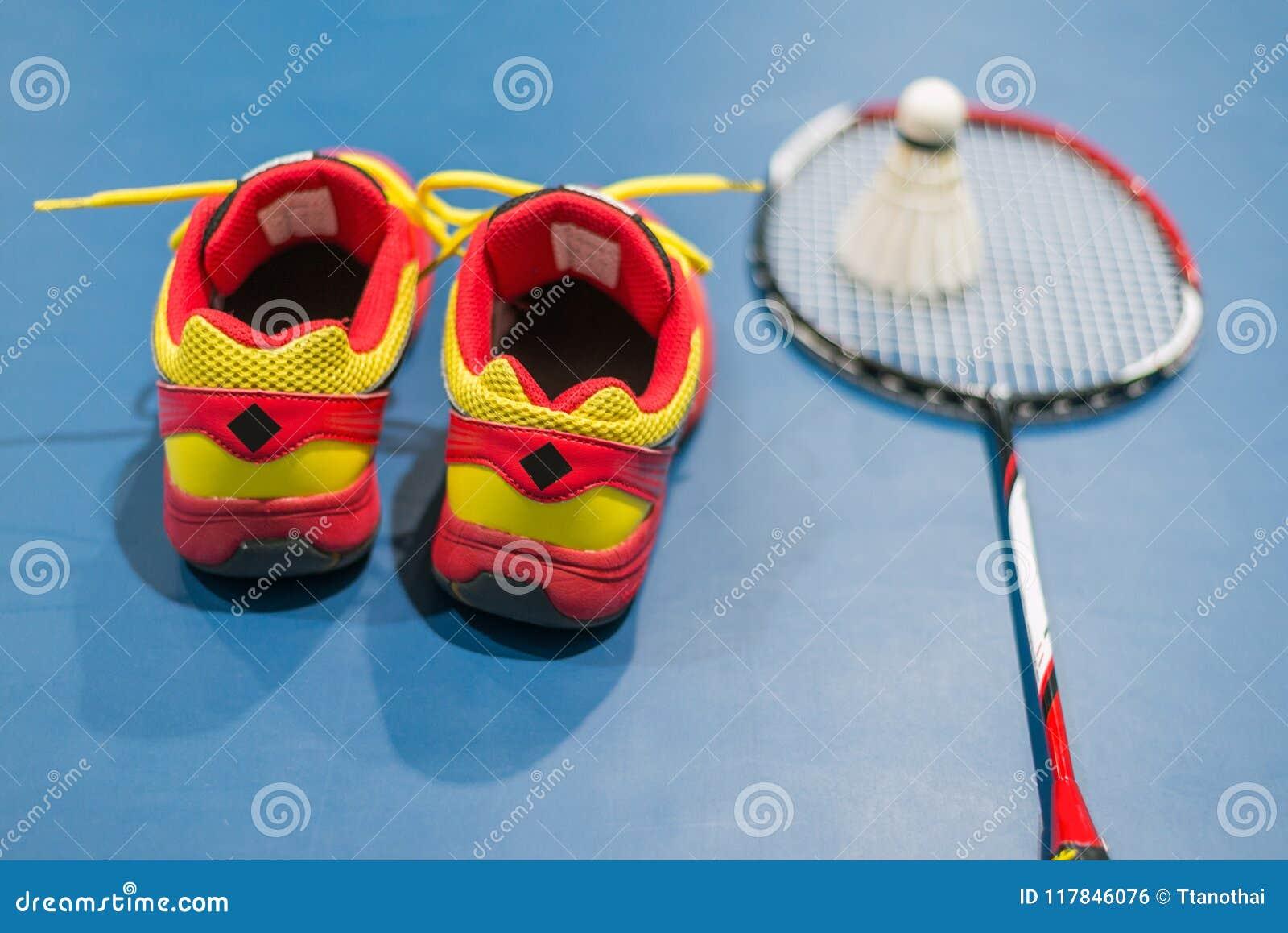 Röda skor för badminton med suddig fjäderboll och racket på domstolen