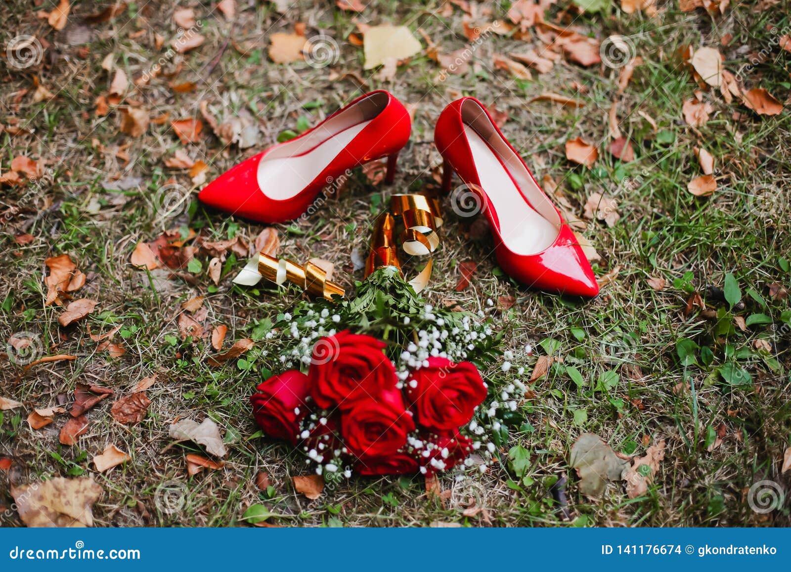 Röda skor och gifta sigbukett av röda rosor på gräset Brud- detaljer